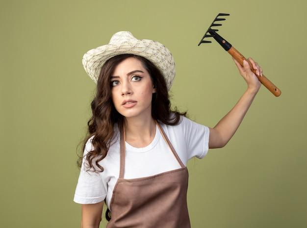 Уверенная молодая женщина-садовник в униформе в садовой шляпе стоит с поднятой рукой, держащей грабли, изолированной на оливково-зеленой стене