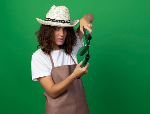 Fiducioso giovane giardiniere femminile in uniforme che indossa il cappello da giardinaggio tenendo i clippers