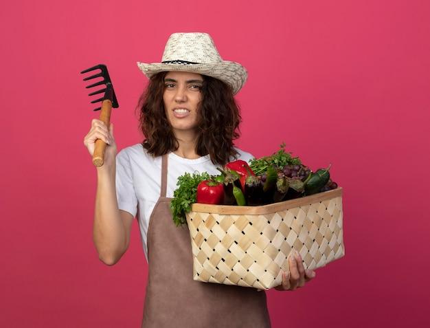 Confident young female gardener in uniform wearing gardening hat holding vegetable basket with rake