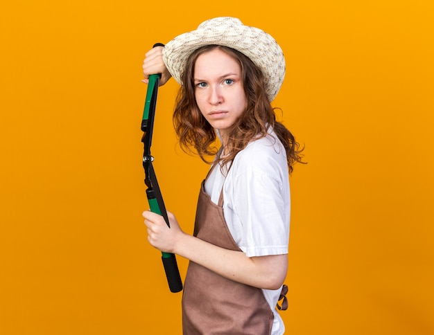 Fiducioso giovane giardiniere femminile che indossa cappello da giardinaggio tenendo la forbice da potatura isolata sulla parete arancione