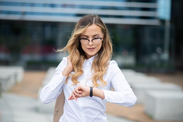 그녀의 시계 야외에서 시간을 확인 자신감 젊은 여성 관리자