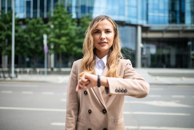 自信を持って若い女性マネージャーが彼女の屋外の時計で時間をチェック