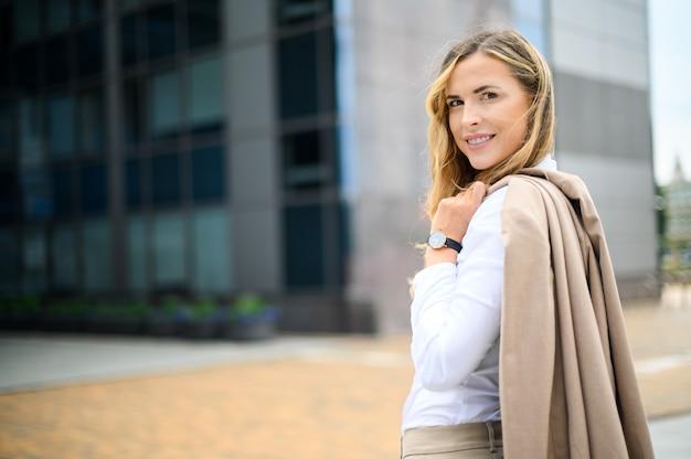 Уверенная молодая женщина-менеджер, держащая куртку на открытом воздухе в современной городской обстановке