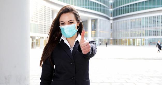 자신감이 젊은 여성 관리자 엄지 손가락을 포기하는 현대 도시 환경에서 야외. 코로나 바이러스 개념