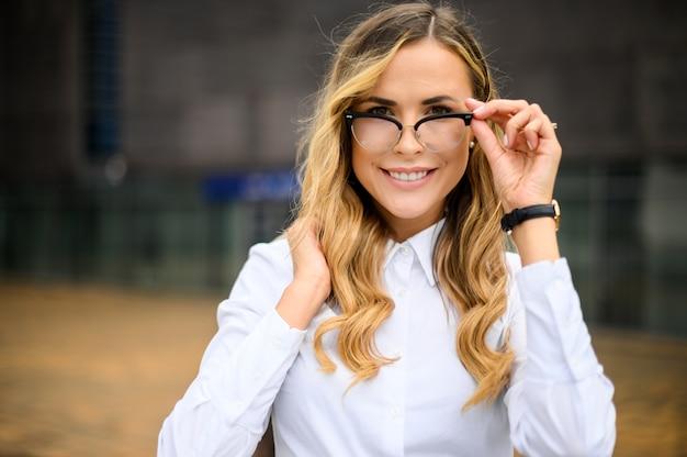 그녀의 안경을 들고 현대 도시 설정 야외 자신감 젊은 여성 관리자