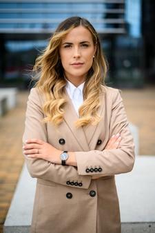 Уверенная молодая женщина-менеджер на открытом воздухе в современных городских условиях
