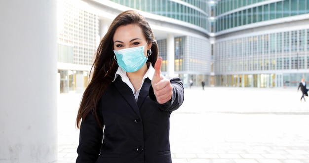 Confident young female manager outdoor in a modern urban setting giving thumbs up. coronavirus concept