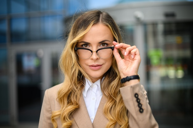 Confident young female manager outdoor in a modern urban setting holding her eyeglasses