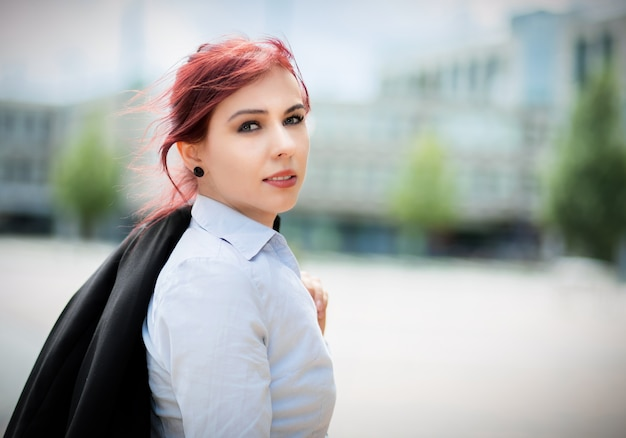 Confident young female manager outdoor in a modern urban setting holding her jacket