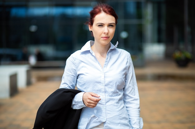 Confident young female manager outdoor in a modern urban setting