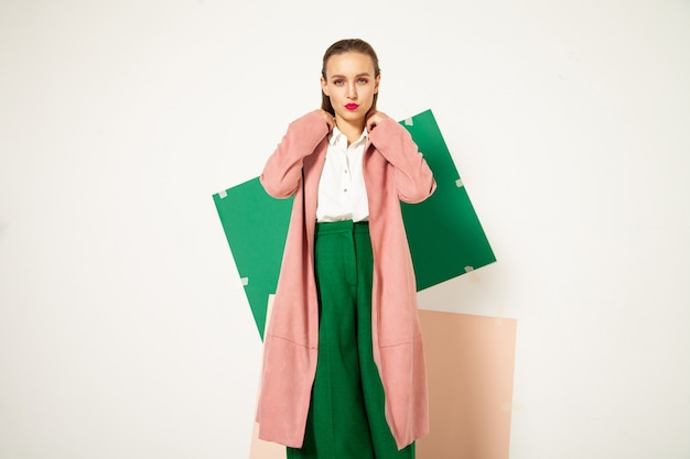 Confident young female model in elegant pastel pink coat and bright green pants representing spring fashion looking away in studio