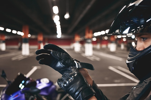 가죽 장갑을 씌우고 세련 된 오토바이 헬멧을 착용하는 자신감이 젊은 여성 레이서 그녀의 파란색 오토바이와 지하 주차장에서 격리 된 포즈. 여자의 손에 선택적 초점