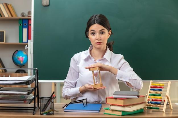 Fiducioso giovane insegnante femminile che tiene la clessidra seduta al tavolo con gli strumenti della scuola in aula