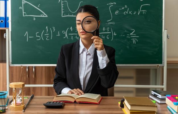 Fiducioso giovane insegnante femminile si siede al tavolo con materiale scolastico guardando davanti con lente d'ingrandimento in classe