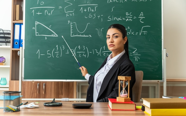 Fiducioso giovane insegnante femminile si siede al tavolo con forniture scolastiche punti alla lavagna con puntatore stick in classe