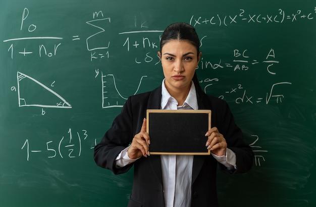 Fiducioso giovane insegnante femminile in piedi davanti alla lavagna con mini lavagna in aula