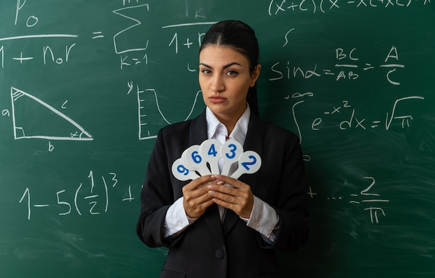 교실에서 숫자 팬을 들고 칠판 앞에 서 있는 자신감 있는 젊은 여성 교사