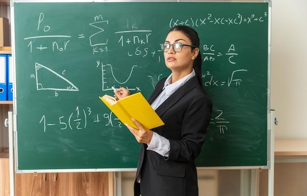 Fiducioso giovane insegnante di sesso femminile con gli occhiali in piedi di fronte alla lavagna tenendo il libro con incagliato per il bordo in aula