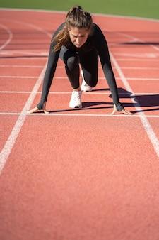 Уверенная молодая спортивная женщина-спринтер на беговой дорожке резинового стадиона или беговой дорожке готовится начать бег