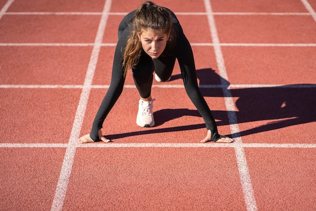Confident young fit woman sprinter on a treadmill rubber stadium or running track getting ready to start run
