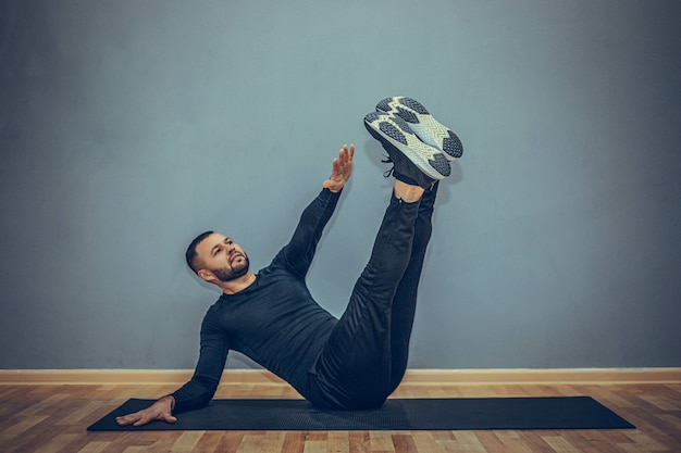 Confident young fitness man exercising on a fitness mat indoors, over gray wall
