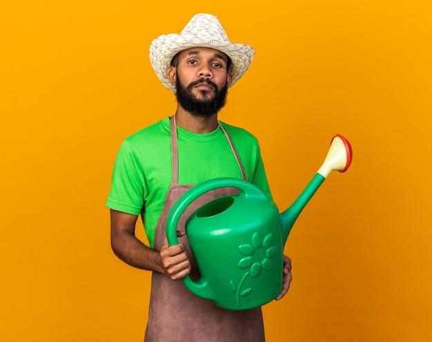 Fiducioso giovane giardiniere afro-americano che indossa un cappello da giardinaggio che tiene in mano un annaffiatoio isolato su un muro arancione