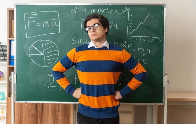 Confident young geometry teacher wearing glasses standing in front of chalkboard in classroom keeping hands on waist looking at front