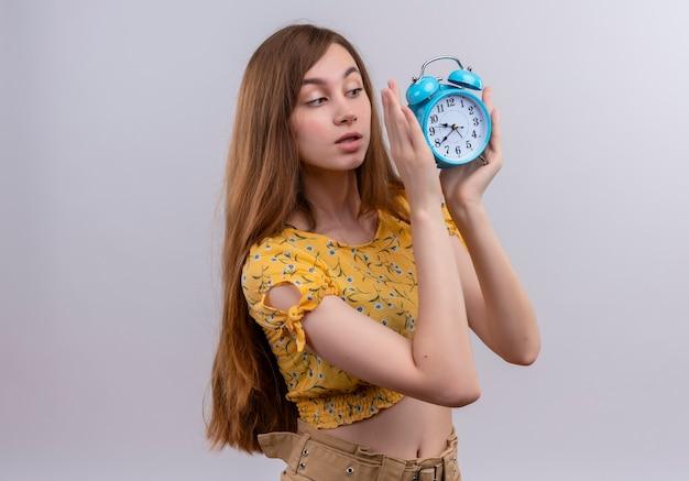 Уверенная молодая девушка держит будильник и смотрит на него с копией пространства