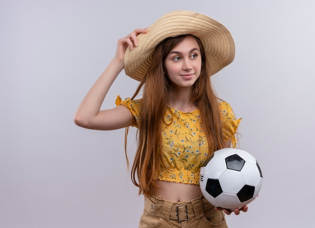 Confident young girl wearing hat holding soccer ball and putting hand on hat on isolated white space