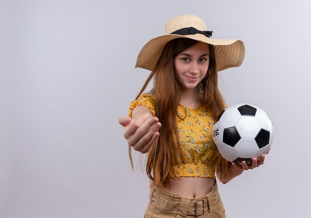 Confident young girl wearing hat holding soccer ball stretching hand  on isolated white space with copy space