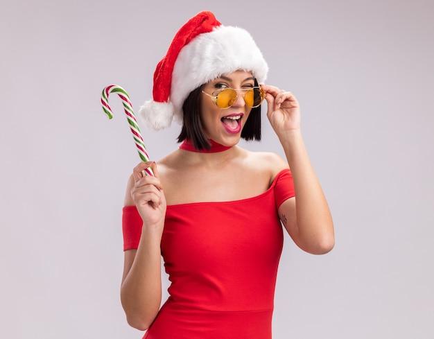 Уверенная молодая девушка в шляпе санта-клауса и очках, держащая рождественскую конфету, глядя в камеру, хватаясь за очки, подмигивая, изолированные на белом фоне