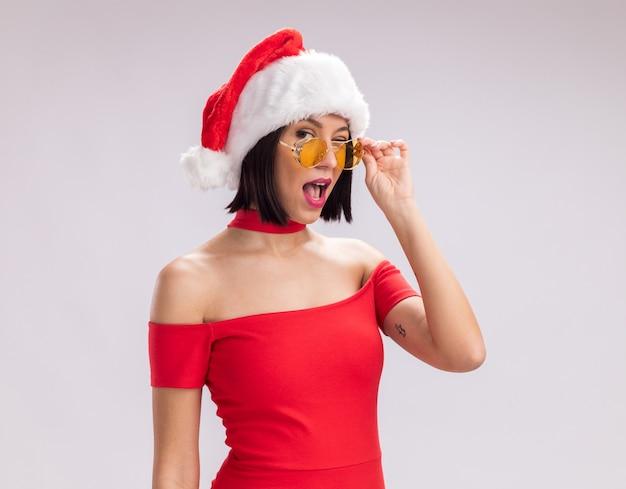 サンタの帽子と白い背景で隔離のまばたきのカメラをつかむ眼鏡を見て眼鏡をかけて自信を持って若い女の子