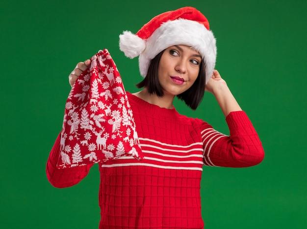 Уверенная молодая девушка в шляпе санта-клауса, держащая рождественский подарочный мешок, глядя на боковую трогательную шляпу, изолированную на зеленой стене
