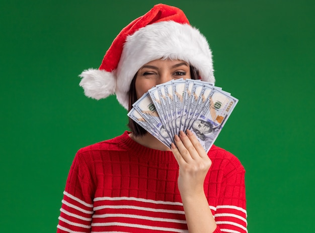 Confident young girl wearing santa hat holding money  from behind it winking isolated on green wall