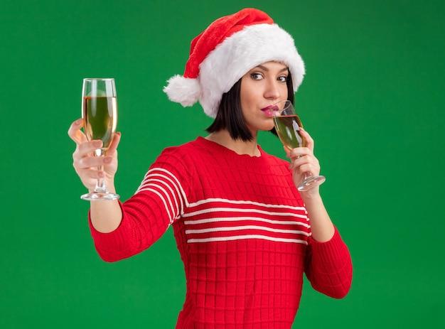 Уверенная в себе молодая девушка в шляпе санта-клауса держит два бокала шампанского, пьет один, протягивая другой, изолированный на зеленой стене