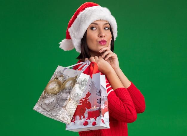 サンタの帽子をかぶった自信を持って若い女の子が横顔に立って、肩にクリスマスギフトバッグを持って、緑の壁に隔離された後ろを見てあごに手を保ちます
