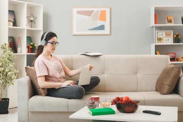 거실에 있는 커피 테이블 뒤에 소파에 앉아 헤드폰을 끼고 노트북을 들고 있는 자신감 있는 어린 소녀