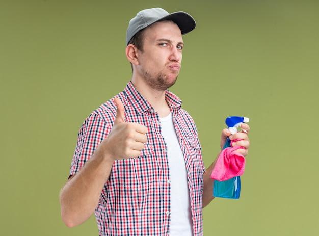自信を持って若い男クリーナーは、オリーブグリーンの背景で隔離の親指を示すぼろきれと洗浄剤を保持しているキャップを着用