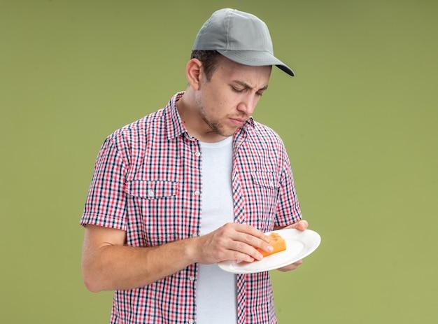 自信を持って若い男クリーナーは、オリーブグリーンの背景に分離されたスポンジでキャップ洗浄皿を身に着けています
