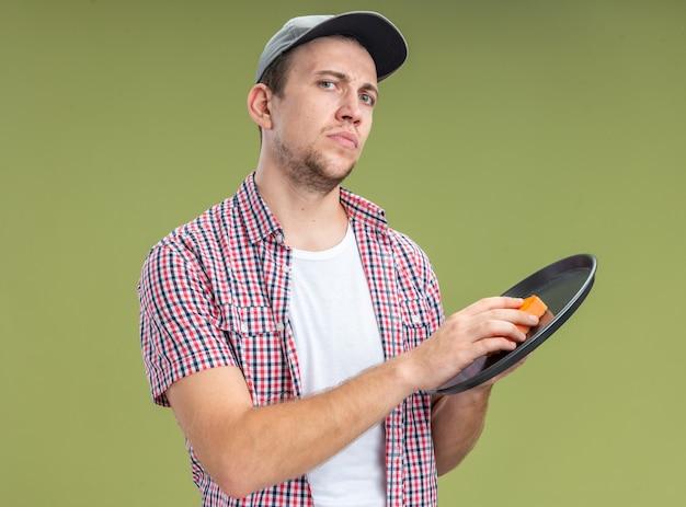 自信を持って若い男クリーナーは、オリーブグリーンの壁に分離されたスポンジとキャップ洗浄トレイを身に着けています