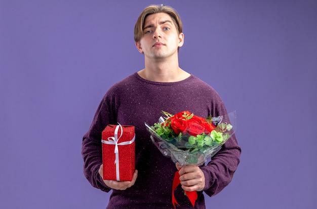 青い背景で隔離の花束とギフトボックスを保持してバレンタインデーに自信を持って若い男
