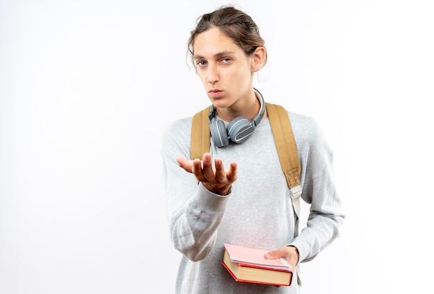 白い壁に隔離された本を保持している首にヘッドフォンでバックパックを身に着けている自信を持って若い男の学生