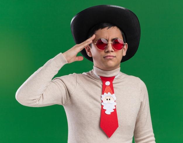 Уверенный молодой парень в шляпе с рождественским галстуком и очками, показывающий жест салюта, изолированный на зеленой стене
