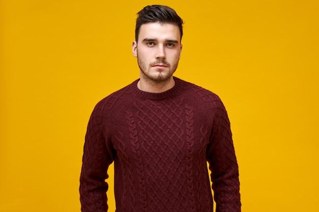 暖かいニットのジャンパーを着て真面目な表情で無精ひげと黒髪の自信を持って若い男。居心地の良いバーガンディのセーターでポーズをとって、厳格な表情を持つブルネットの男