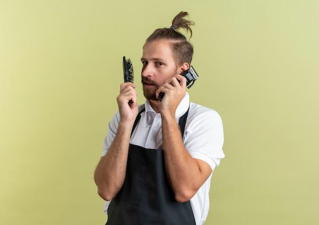 Уверенный молодой красивый парикмахер, держащий расческу и машинки для стрижки волос, притворяется, что разговаривает по телефону, используя машинку для стрижки волос в качестве телефона, изолированного на оливково-зеленом с копией пространства