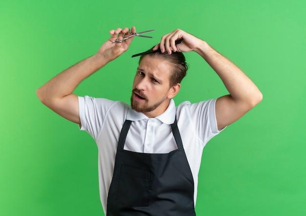 Уверенный молодой красивый парикмахер в униформе, расчесывающий волосы и держащий ножницы, изолированные на зеленом