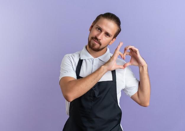 Fiducioso giovane barbiere bello che indossa uniforme facendo segno di cuore isolato su viola con copia spazio