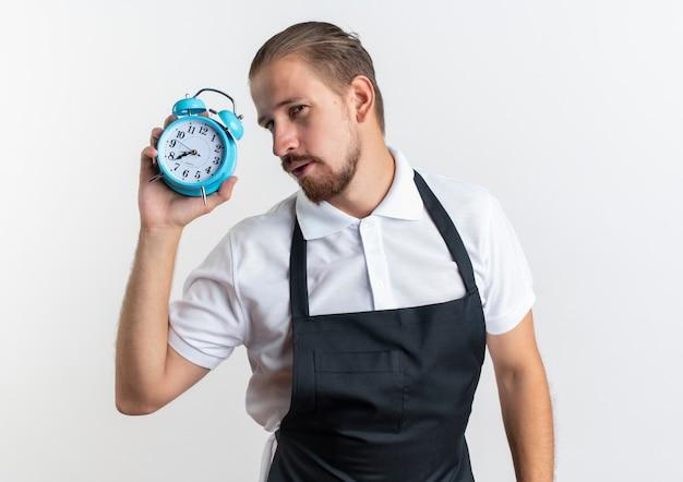 Fiducioso giovane barbiere bello che indossa la sveglia uniforme della holding isolata su bianco