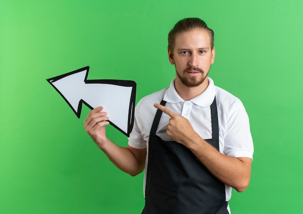 Confident young handsome barber wearing uniform holding arrow mark and pointing at side isolated on green