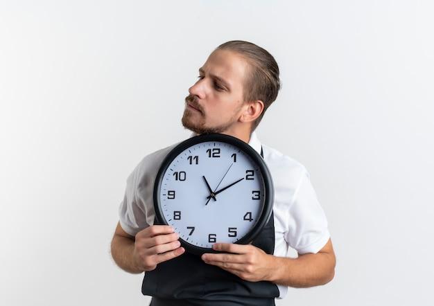 Fiducioso giovane barbiere bello che indossa l'orologio uniforme della tenuta e guardando il lato isolato su bianco con lo spazio della copia